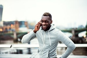 Black man runner with smartphone on