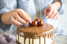 Woman decorating cake by  in Food & Drink