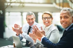 Three mature businesspeople clapping