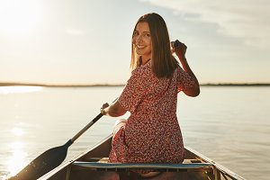 Smiling young woman canoeing on a st