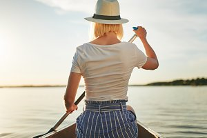 Young woman canoeing on a scenic lak