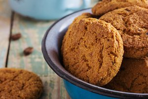 Oatmeal cookies in a metal bowl with coffee