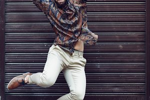 Young bearded man jumping in urban b