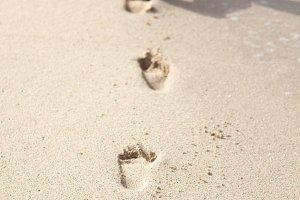Child legs running on the beach.