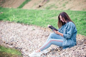 Relaxed young woman reading book