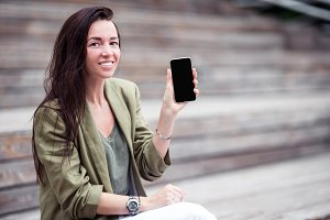 Happy woman with smartphone outdoors