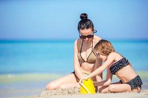 Mother and little kid enjoying beach