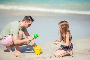 Father and little kid enjoying beach