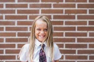 Happy cute schoolgirl posing in a st