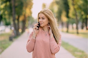 young girl speaks on phone outdoor