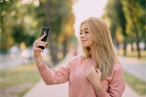 girl makes selfie on town alley