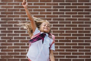Happy cute schoolgirl jumping in a s