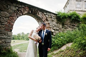 Wedding couple under arch of gate of