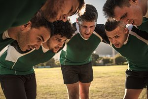 Rugby team in huddle discussing