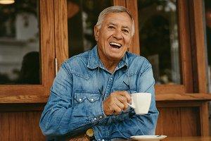 Cheerful senior man having coffee