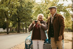 Senior couple taking picture on car