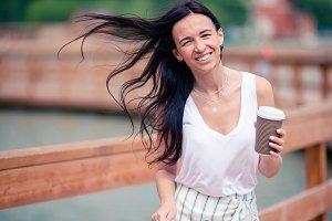 Happy young urban woman drinking cof