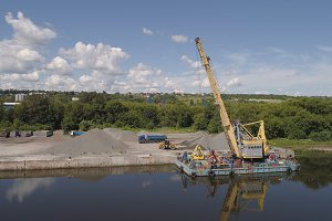 River crane excavator on barge.
