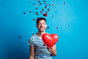 A young man in love holding red