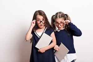 Two small surprised schoolgirls with
