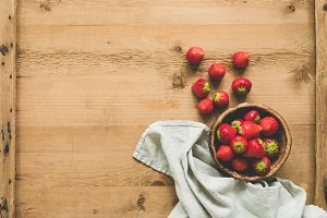 Strawberries in bowl on wooden table