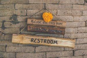 Wooden plate restroom sign.