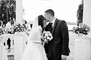 Wedding couple kissed under white ar