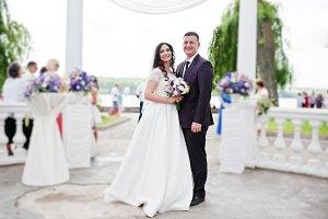 Wedding couple posed under white arc
