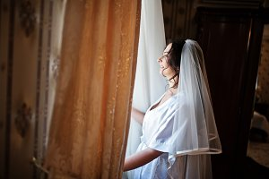 Brunette bride looking at window on