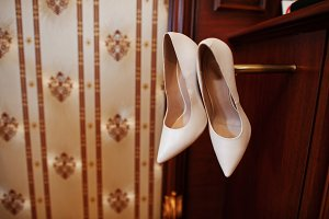 Beige luxury wedding shoes at wooden