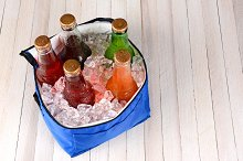 Cooler With Ice and Soda Bottles