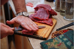 Butcher man cutting meat on the