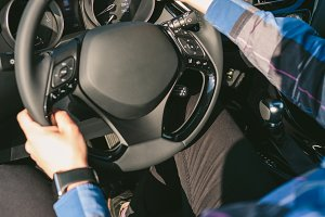 Young man holding steering wheel whi