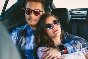 Young couple resting in the backseat