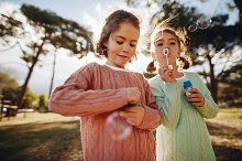 Sisters playing with soap bubbles by  in People