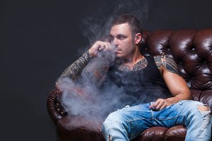 Vaper. The man with tattoos sits on