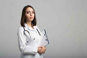 smiling doctor woman on a gray back