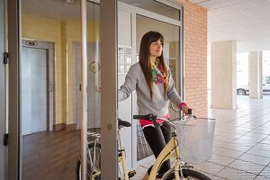 Girl with fixie bike opening door