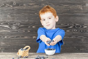 child with blueberry