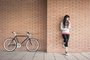 Woman with bike over a brick wall