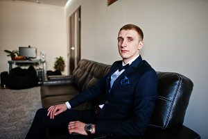 Young stylish groom sitting on leath