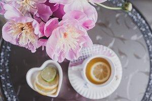 Bouquet of peonies, tea with lemon,