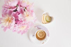 Bouquet of peonies, tea with lemon
