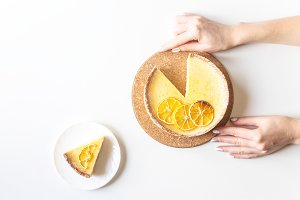 Lemon tart on a white table in hands