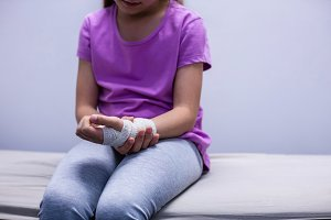 Girl with injured hand sitting