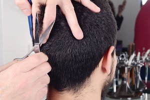 Young man having a haircut with scis