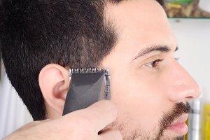 Man having a haircut with hair clipp