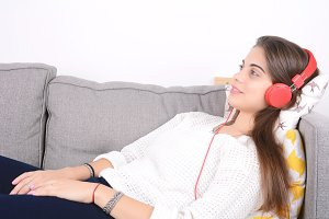 Woman listening music on couch.