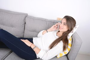 Woman talking on phone on couch.