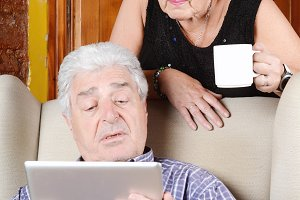 Old couple using tablet.